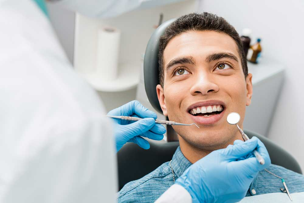 cheerful african american man with during examination in dental clinic